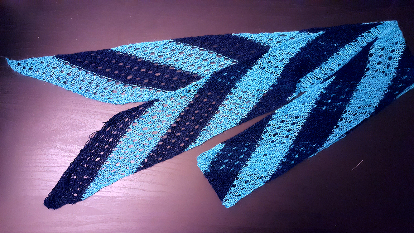 A light blue and dark blue striped scarf with angled stripes on a black surface.