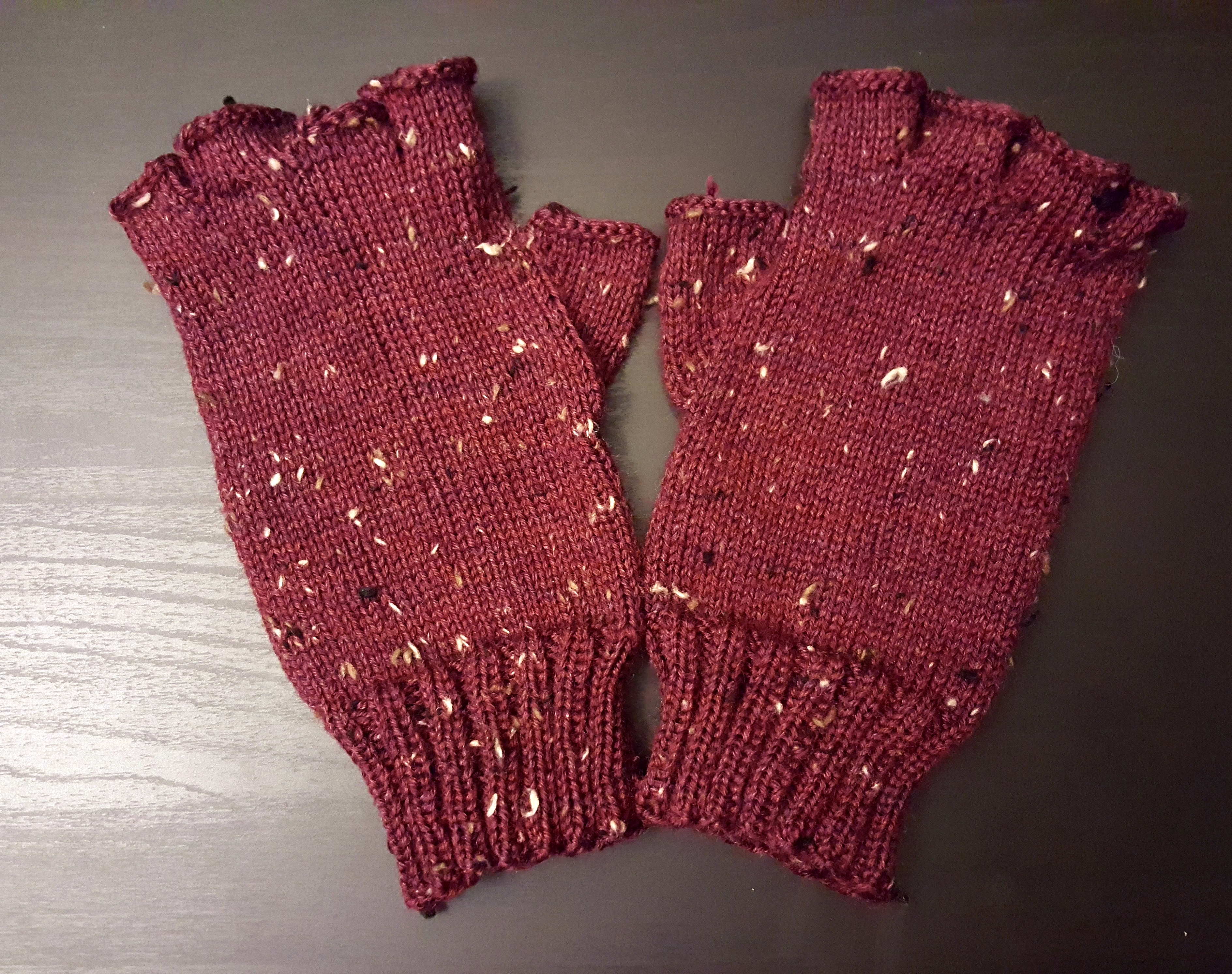 Red-Purple tweed fingerless gloves on a black surface.