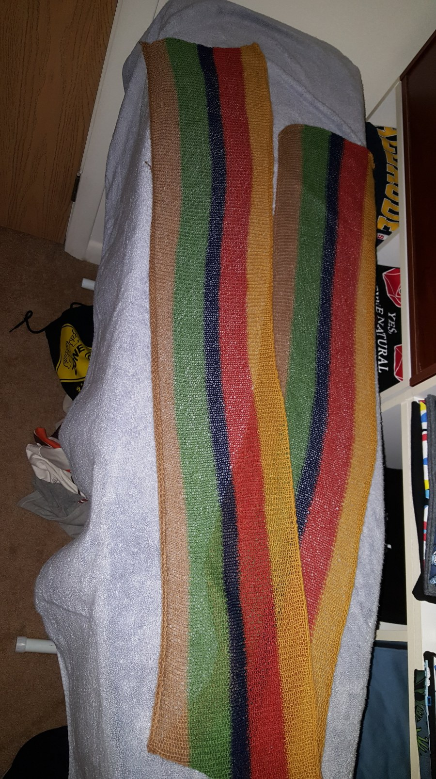 A scarf with tan, green, blue, red, and gold stripes that run its length on a light blue ironing board with other stuff in the background.